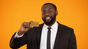 Smiling confident afro-american businessman showing gold card and ok gesture. Stock footage stock video