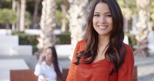 Smiling confident attractive young woman. With long brunette hair standing in an urban square looking at the camera with a warm friendly smile  upper body stock video