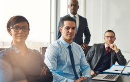 Smiling confident business team seated at a table. Smiling confident multiracial business team seated at a table in a conference room in the office making Stock Images
