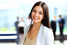Smiling confident business woman. Looking at camera with her colleagues in background at office Royalty Free Stock Image