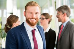 Smiling businessman and his team in the background royalty free stock photos
