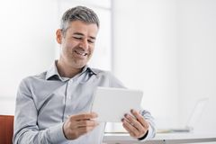Smiling confident businessman using a touch screen tablet in the office, he is watching a video and enjoying royalty free stock photos