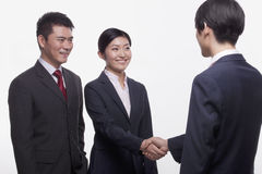 Smiling and confident businesspeople meeting and shaking hands, studio shot Stock Photo