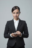 Smiling confident businesswoman using touch screen mobile phone Royalty Free Stock Image