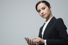 Smiling confident businesswoman using touch screen mobile phone. Smiling confident business woman using touch screen mobile phone Royalty Free Stock Photo
