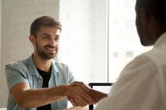 Smiling confident caucasian candidate handshaking african employ. Smiling confident caucasian candidate handshaking african hr manager at job interview, white royalty free stock photos