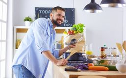 Smiling and confident chef standing in a large kitchen tasting a cooked dish royalty free stock images