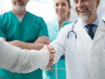 Confident doctor shaking patient`s hand stock photography