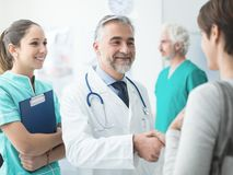 Confident doctor shaking patient`s hand royalty free stock photos