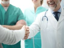 Confident doctor shaking patient`s hand stock image