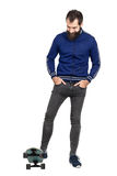 Smiling confident hipster wearing blue tracksuit jacket and tight jeans standing on skateboard. Full body length portrait isolated over white studio background Royalty Free Stock Image