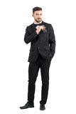 Smiling confident luxurious man in suit putting cellphone in suit pocket looking at camera Royalty Free Stock Photos