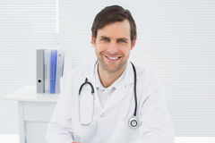 Smiling confident male doctor in medical office Royalty Free Stock Images