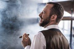 Smiling confident man smoking cigar indoors. Side view of smiling confident man smoking cigar indoors Stock Photography