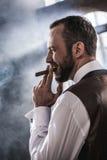 Smiling confident man smoking cigar indoors. Side view of smiling confident man smoking cigar indoors Stock Photo