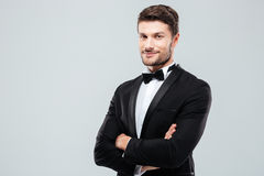 Smiling confident man in tuxedo standing with arms crossed. Smiling confident young man in tuxedo standing with arms crossed over white background Stock Photo