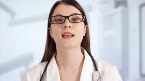 Female doctor in hospital room talking with patient via messenger app. Woman physician at work. Smiling confident professional female doctor with stethoscope stock video