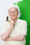 Smiling confident senior man with a hammer. Dangled over his shoulder standing in front of a half painted green and white wall Stock Photos