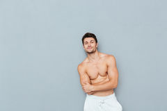 Smiling confident shirtless young man standing with arms crossed Stock Photo