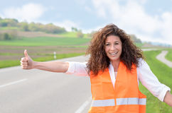 Smiling confident woman hitching a lift Royalty Free Stock Images