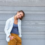 Smiling confident woman leaning against wall. Portrait of smiling confident woman leaning against wall Royalty Free Stock Photo