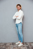Smiling confident young man in hat standing with hands folded Royalty Free Stock Photo