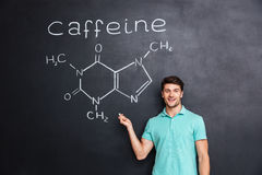 Smiling confident young student showing chemical structure of caffeine molecule Stock Photography