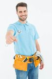 Smiling construciton worker holding wrench. Portrait of smiling construciton worker holding wrench against white background Royalty Free Stock Photography