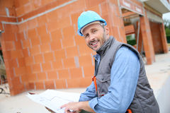 Smiling construction manager with blue print Royalty Free Stock Photo