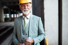 Smiling construction manager, engineer, businessman, architect standing on construction site royalty free stock image