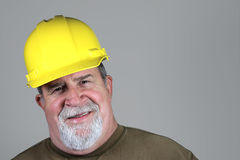 Smiling Construction Worker. A smiling construction worker in a yellow hard hat Stock Photography