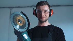 Smiling construction worker with angle grinder. Young man construction worker with angle grinder machine in safety ear muffs and black t-shirt, standing and stock video