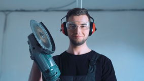 Smiling construction worker with angle grinder. Young man construction worker with angle grinder machine in safety ear muffs and black t-shirt, standing and stock footage