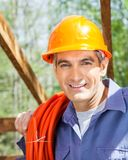 Smiling Construction Worker Carrying Rolled Pipe Royalty Free Stock Image