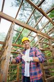 Smiling Construction Worker Hammering In Timber Royalty Free Stock Photo