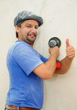 Smiling construction worker hand-polishing the wall Stock Image