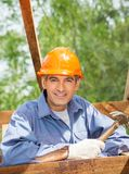 Smiling Construction Worker Holding Hammer At Site Royalty Free Stock Photography