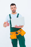Smiling construction worker holding laptop Stock Image