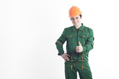 Smiling construction worker holding a thumb up. Smiling construction worker in working order and a helmet holding a thumb up and shows, that all will be well Stock Images