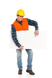 Smiling construction worker pointing at banner. Royalty Free Stock Photo