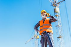 Smiling construction worker in reflective vest and hardhat talking. On smartphone royalty free stock photo