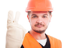Smiling construction worker showing two fingers. Or indicate the second point on white background Stock Image