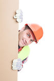 Smiling construction worker standing behind banner. Isolated on white with copy space Royalty Free Stock Images