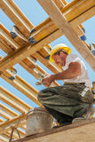Smiling construction worker under slab girders. Smiling authentic construction builder working with clamps underneath slab formwork beams Royalty Free Stock Photos