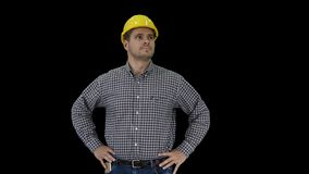 Smiling construction worker in yellow helmet looking at perfect well built object Hands on hips, Alpha Channel. On Alpha Matte. Medium shot. Walking in and out stock video footage