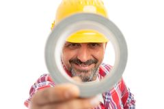 Constructor looking through duct tape. Smiling constructor looking through duct tape isolated on white studio background royalty free stock images
