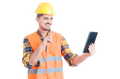 Smiling constructor using tablet and showing peace or victory ge Stock Photos
