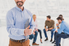 Smiling consultor giving thumb up gesture Stock Photo