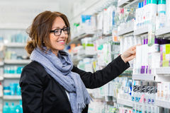 Smiling Consumer Choosing Product In Pharmacy Royalty Free Stock Photos