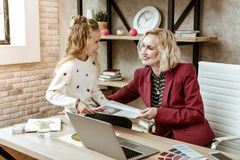 Smiling contented blonde mother having fun with her positive daughter at work. Observing articles. Smiling contented blonde mother having fun with her positive stock image